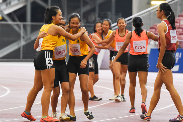 Competitors of the B Division girls' 100m hurdles final embrace after the race. (Photo X © Iman Hashim/Red Sports)