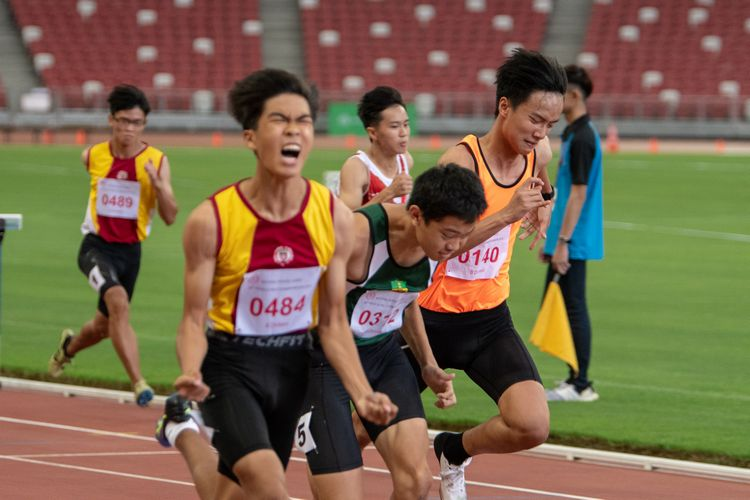 Gabriel Lee (#484) of Victoria School celebrates as he crosses the finish line. Behind him, Wellington Ho (#312) of RI and Lai Yiyi (#140) of Singapore Sports School go shoulder-to-shoulder, each in a last-minute attempt to overtake the other.