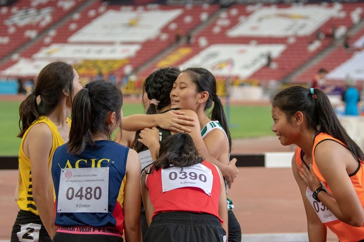 Valencia Ho (#410) of RI and Natalie Shek (#434) of St. Joseph's Institution (international) embrace after the A Division Girls' 100m hurdles final.