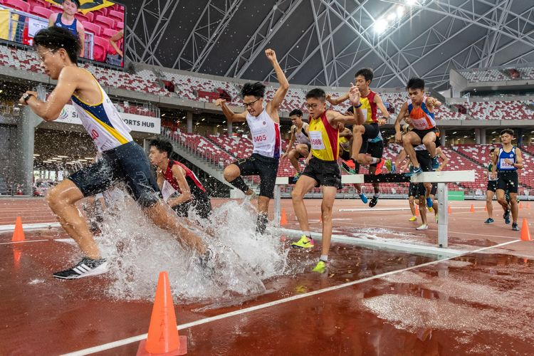 The B Division boys at the water jump of the 2000m steeplechase final.
