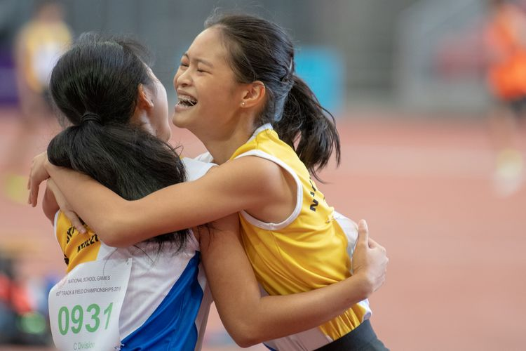Eleana Goh (#925) embraces fellow NYGH runner Qiu Xinyu (#931) after the C Division Girls' 100m final.