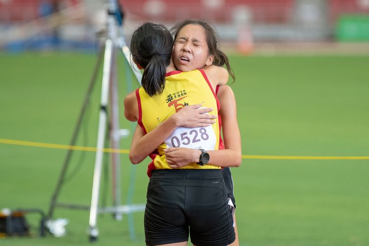 HCI teammates Vera Wah (#528) and Toh Pei Xuan (#527) embrace after the A Division Girls' 1500m final.
