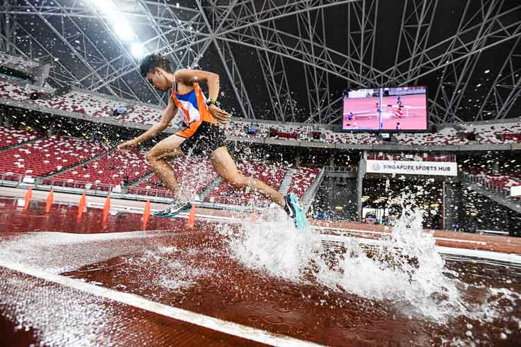 Loh Wei Long of Yuan Ching Secondary School rises above the water, on his way to winning the 2000m Steeplechase final. (Photo 1 © Stefanus Ian)