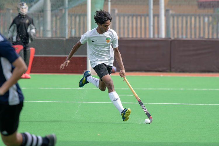 Akash Chandra (#82) of RI dribbles the ball as he runs, his boots kicking up water from the wet pitch.