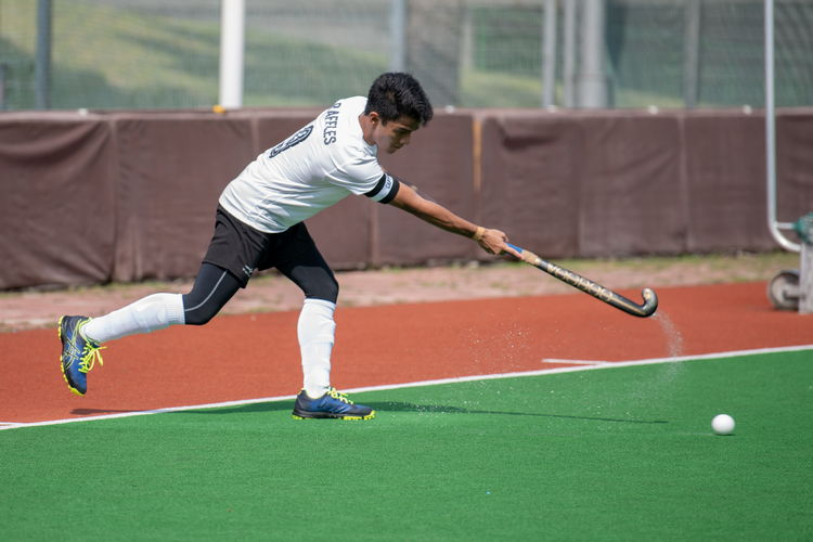 Raffles captain Raziq Noor (#9) takes a short corner, his stick flinging water from the wet field.
