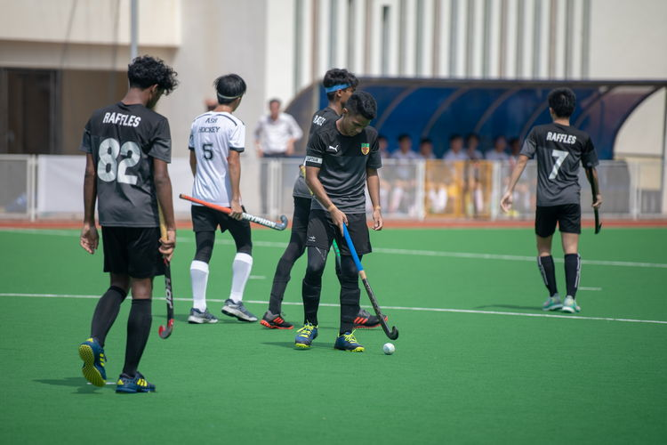 Raffles players prepare to restart the game after an ASRJC short corner. Captain Raziq Noor (RI #9, in the middle) taps the ball into place.