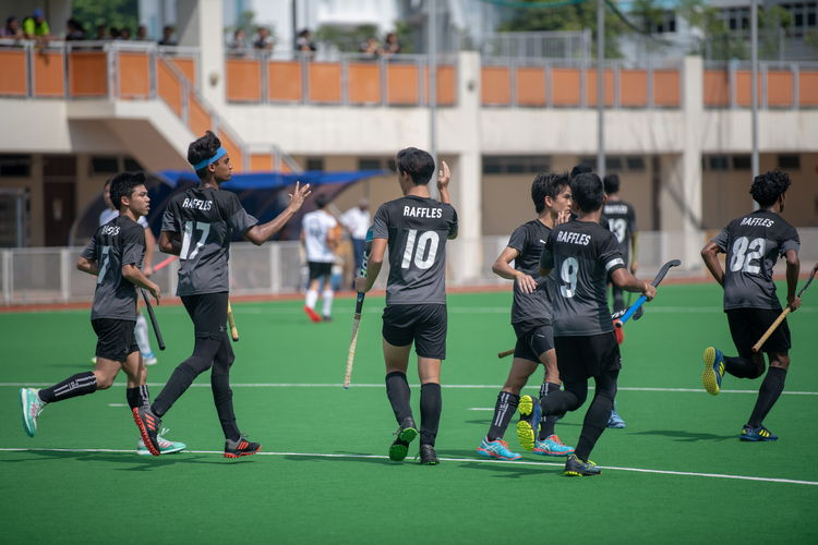 Raffles players trade brief high-fives after Alton Chua's (RI #10) icebreaking goal.