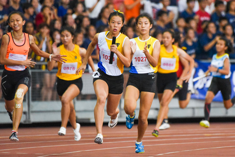 NYGH's Bernice Liew (#1027) hands over to anchor Elizabeth-Ann Tan (#1038) in the B Division girls' 4x100m relay. Their team clinched the gold in 48.30s, the second-fastest timing clocked in the history of this event. (Photo 1 © Iman Hashim/Red Sports)
