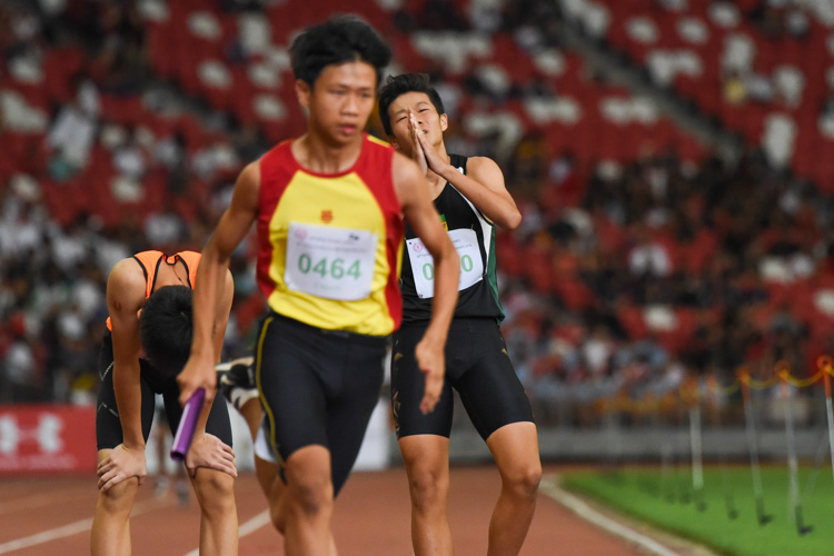 Marcus Heng (#220) of RI dissatisfied with his third leg in the C Division boys' 4x400m relay, as HCI's Zak Tng starts his run. (Photo 1 © Iman Hashim/Red Sports)