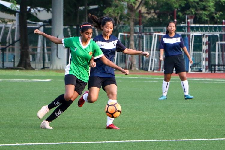 Joelle Teo (SAJC #11) attempts to dribble the ball under pressure from Milanpreet Kaur Bajwa (RI #13). (Photo 2 © Clara Lau/REDintern)
