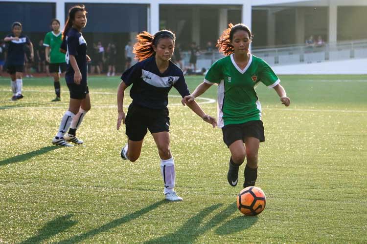 Seow Si Min (RI #18) dribbles the ball down the wing shadowed by Clae Kho (SAJC #9). (Photo 6 © Clara Lau/REDintern)