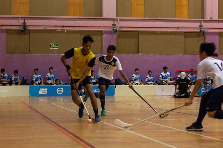 Mikail Sumono Ramli (VJC #25) holds the ball as two TMJC players begin to surround him. (Photo 11 © REDintern Jordan Lim)