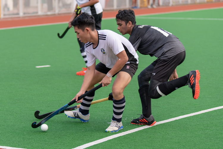 Kevin Saji (RI #13) attempts to take the ball away from Nicholas Yeo (#21) of SAJC.