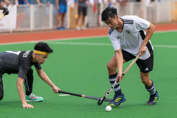 Ethan Tan (RI #7) faces down Ray Au (SA #9), who trips on his opponent's stick...