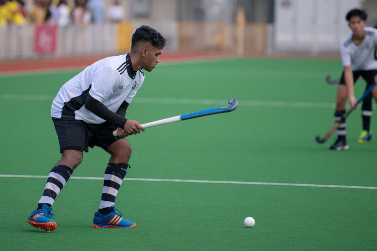 Sailesh Kumar (SA #5) raises his stick to smack the ball.