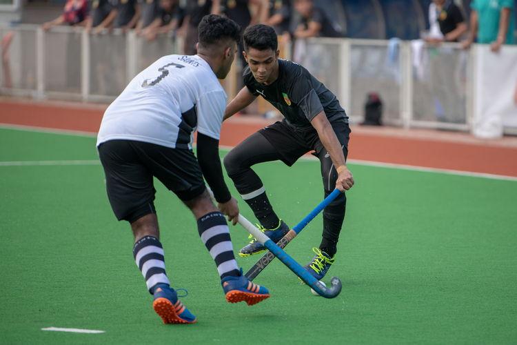 Raziq Noor (RI #9) and Sailesh Kumar (SA #5) cross sticks in a battle over the ball.