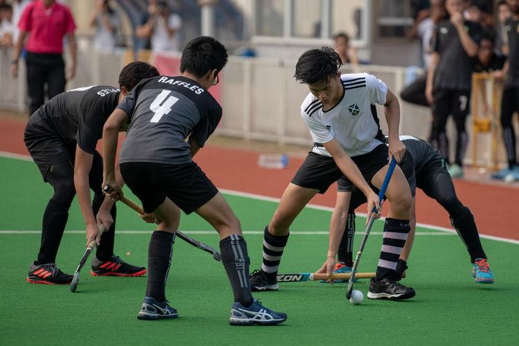 Elliot Chong (SA #14) evades a group of Raffles players.