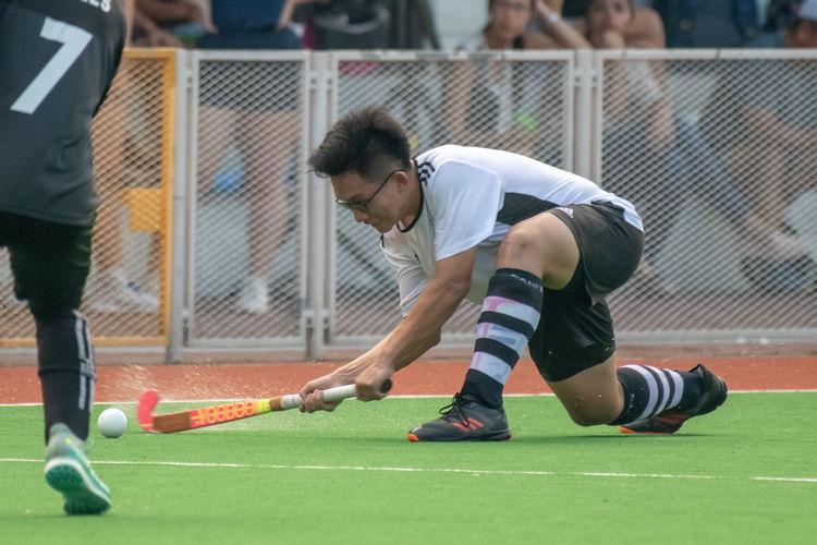 Kai Yao (SA #15) sinks low to smack the ball across the field.