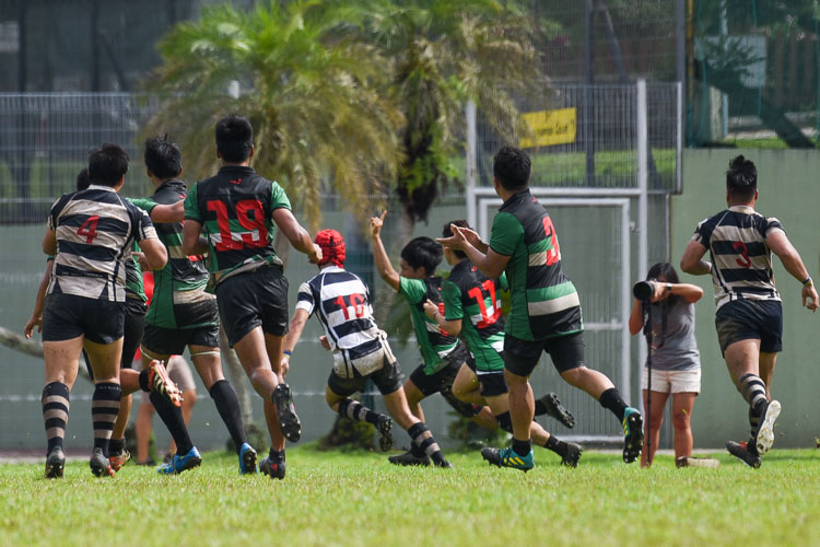 Jonathan Cristopher Lim (RI #9) raises his arm in celebration before touching down for RI's second try in the game. (Photo 1 © Iman Hashim/Red Sports)