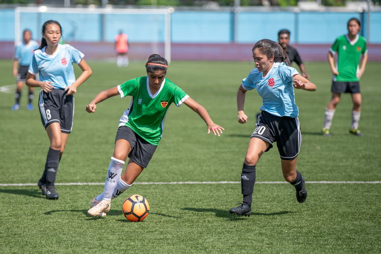 Milanpreet Bajwa (RI #13) tries to cut into the center to take a shot, but she's faced down by HCI's Drew Saurajen (#20).