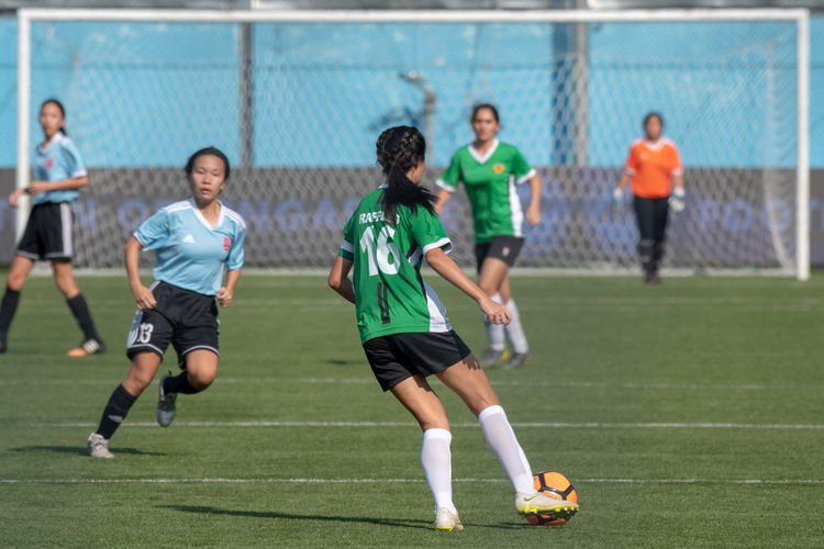Christie Soo (RI #16) looks to pass the ball far forwards.