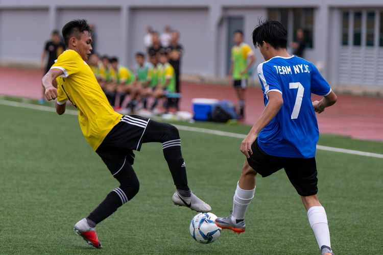Sirhan Muzaffar (VJC #17) inserts a foot into the path of Javier Chua's (NYJC #7) ball in an attempt to take it away from him.