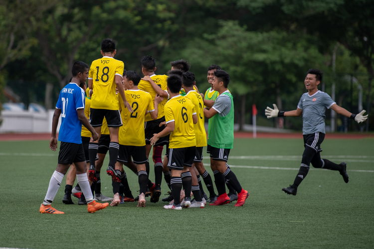 The VJC players joyfully celebrating their 4-0 victory over NYJC. A lone NYJC player strides past the celebrating group.