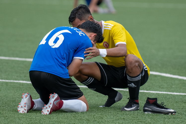 Adam B Johan (VJC #7) squats to comfort a grieving Julio Tan (NYJC #16).