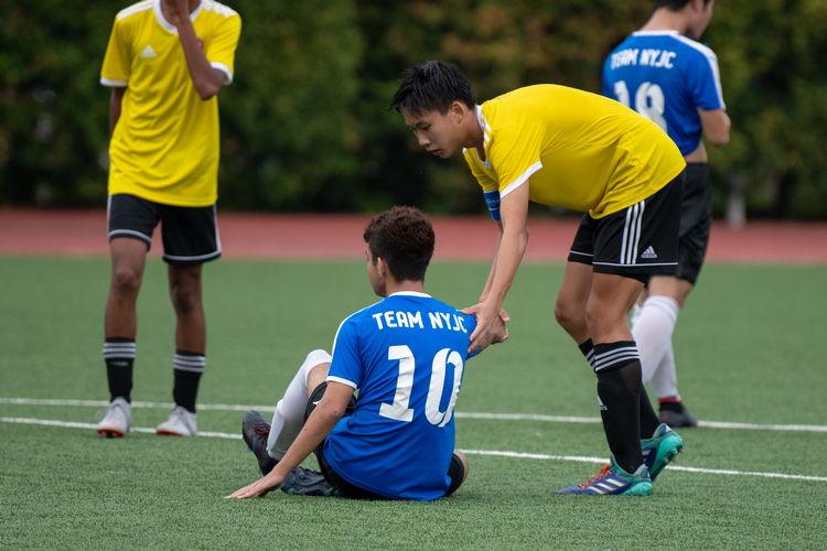 VJC captain Jeremy Loke (#4) helps Shaked Shalev (NYJC #10) up after the game.