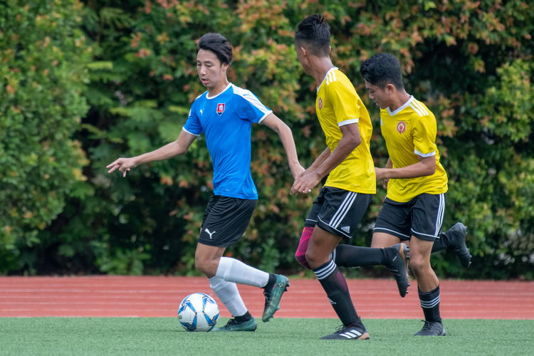 Gabriel Lee (NYJC #2) dribbles up the right wing, shadowed by Victoria players Akmal Yashir (#5) and Imran Ashry (#16).