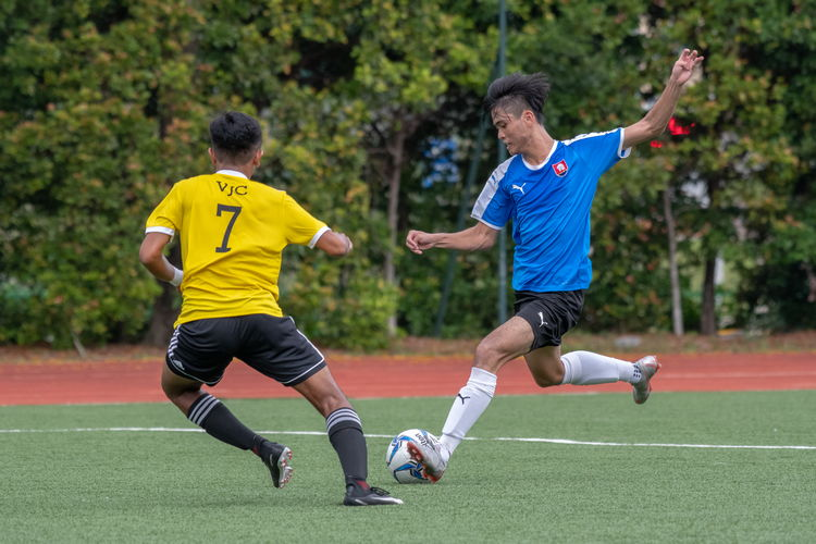 Neo Wei Yang (NYJC #17) attempts to put some distance between his goal and the ball, opposed by VJC player Adam B Johan (#7).