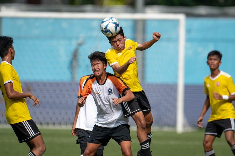 Imran Ashry (VJC #16) leaps against Joshua Tan (SAJC #1) to header a ball.