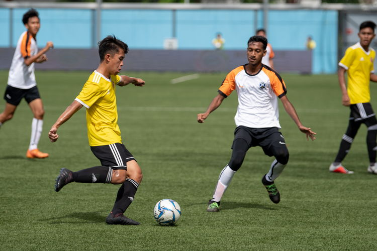 Artemus See (VJC #19) attempts to dribble past SAJC player Naeemur Rahman (#14).