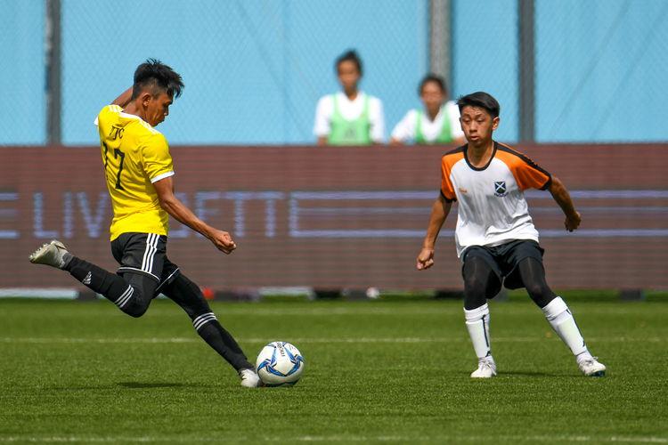 Sirhan Muzaffar (VJC #17) readies to kick the ball; Benitius Soegiono (SAJC #44) watches him.