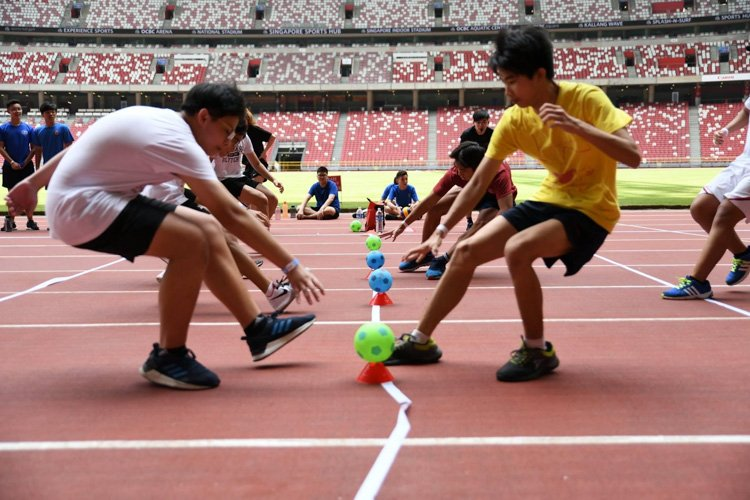 As the whistle sounds in a game of dodgeball, teams race to the middle line and grab the plastic balls, ready to attack. (Photo 2 © HIGHER)