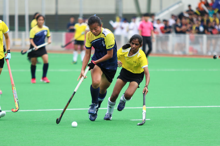 Valerie Koh (EJC #17) dribbles the ball towards goal under the close watch of Mylsamy Boojha Rukmi (VJC #2). (Photo 1 © Clara Lau/REDintern)