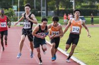 Justin Chan (#204) of NUS and Wayne Yap (#180) of NTU receive the baton almost simultaneously between the second and third legs of the Men's 4x400m Relay timed finals. NUS went on to win gold while NTU finished fifth. (Photo 1 © Iman Hashim/Red Sports)