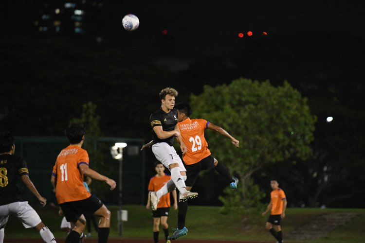 Marco Lekkas (SMU #7) going up for a header against Ahmad Taufiq (NUS #29). National University of Singapore and Singapore Management University played out an exciting but ultimately goalless 0-0 draw in the Singapore University Games Football Championship. (Photo 1 &copy Stefanus Ian/Red Sports)