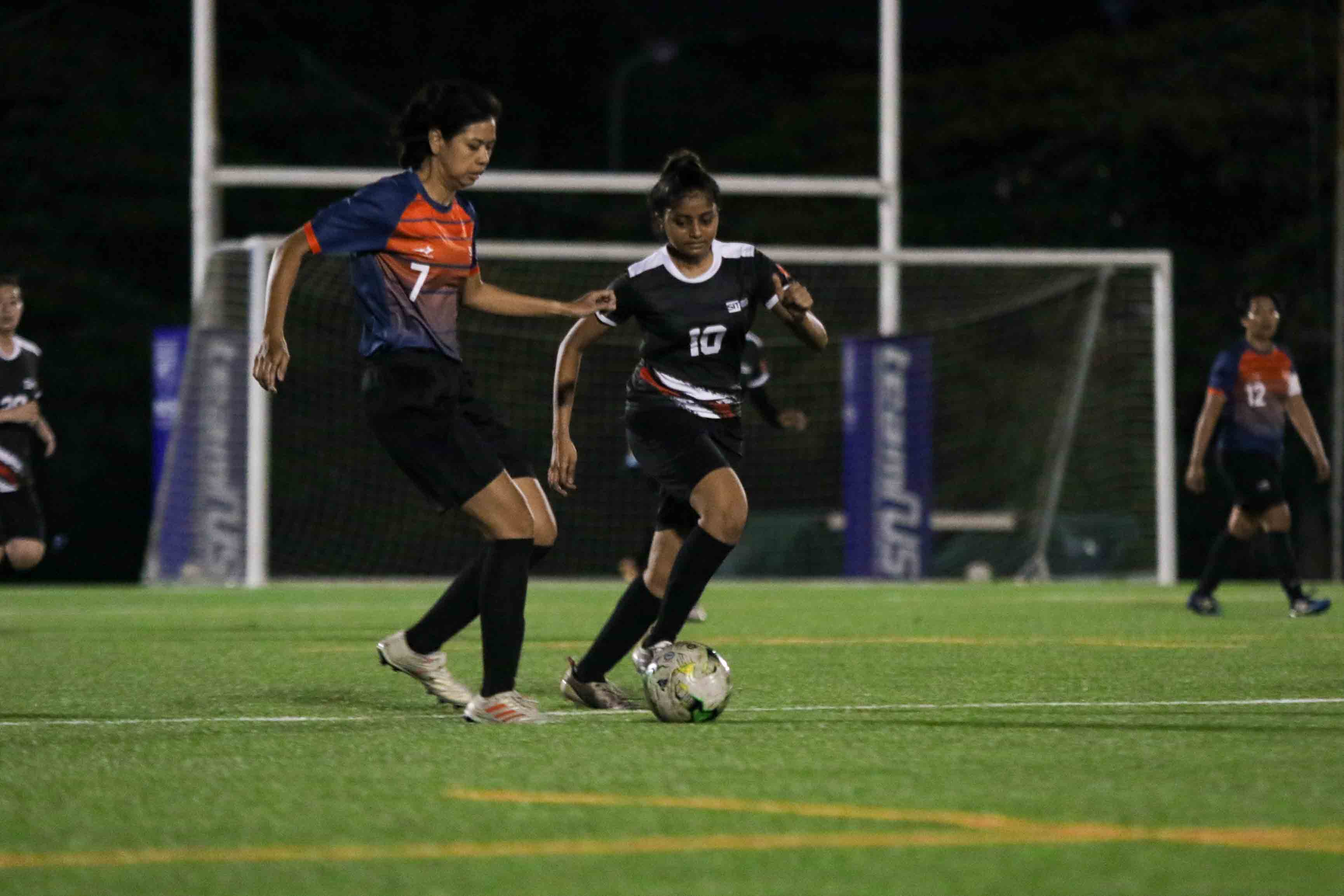 Zulaikha Bte Mohd Nasir (SUSS #7) protects the ball from Krithi (SIT #10). (Photo 4 © Clara Lau/Red Sports)