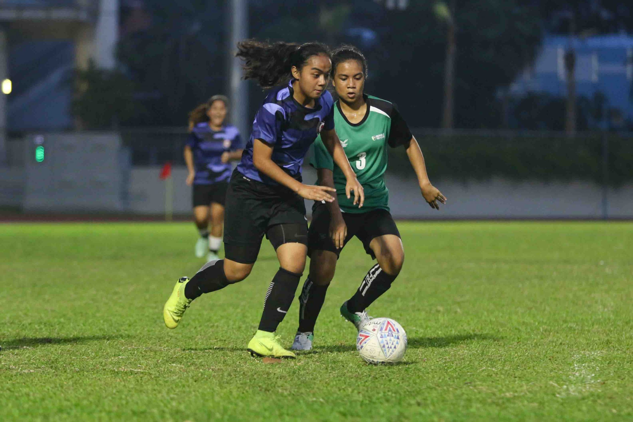 Siti Nor Aqilah Binte Md Shazali (ITE #14) dribbles the ball under pressure from Nurul Ardian Binte Baharrudin (RP #3). (Photo 2 © Clara Lau/Red Sports)