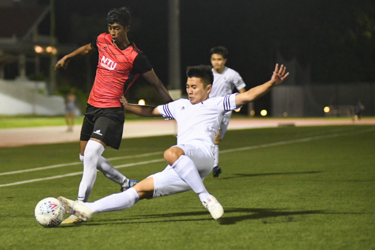 Jerrick Chan (SMU #4) making a sliding tackle during the match. NTU put up an attacking exhibition to win 6-1 against SMU in their opening IVP Football competition. (Photo 1 © Stefanus Ian/Red Sports)
