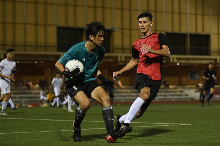 SMU's Ragene Ng (#1) collecting the ball calmly during the match despite pressure from Niels Wallace Aplin (NTU #9, in red). NTU put up an attacking exhibition to win 6-1 against SMU in their opening IVP Football competition. (Photo 1 © Stefanus Ian/Red Sports)