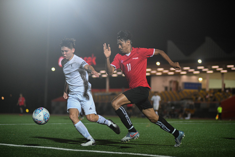 Muhammad Syukri (TP #11, in red) chasing down a loose ball in the SMU penalty box. Temasek Polytechnic cruised to a 5-0 win over Singapore Management University to book their place in the semi-final of the Institute-Varsity-Polytechnic football tournament. (Photo 1 © Stefanus Ian/Red Sports)