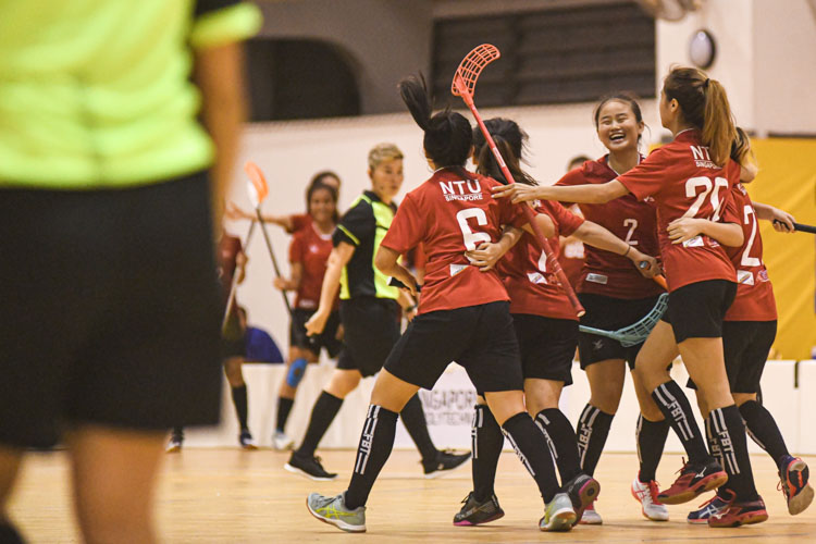 NTU players celebrating their opening goal against RP. Nanyang Technological University completed their Institute-Varsity-Polytechnic (IVP) floorball season in a close-to-perfect run against Republic Polytechnic. The girls in red dominated the match with a 2-0 win as they were crowned 2019/20 IVP champions.(Photo 1 © Stefanus Ian/Red Sports)