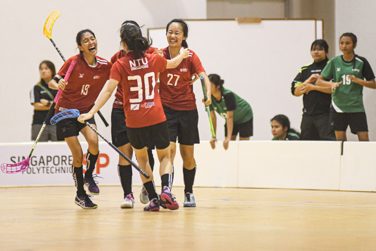 NTU players celebrating Cheryl Seet's (NTU #27) goal, which proved to be the winning goal of the match. Nanyang Technological University completed their Institute-Varsity-Polytechnic (IVP) floorball season in a close-to-perfect run against Republic Polytechnic. The girls in red dominated the match with a 2-0 win as they were crowned 2019/20 IVP champions.(Photo 1 © Stefanus Ian/Red Sports)