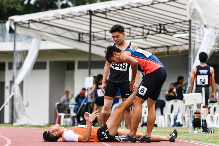 IVP Men's 200m champion Muhammad Naqib Asmin (in red and blue) helps competitor and silver medalist Dexter Lin ( in orange) to stretch off a cramp. (Photo 1 © Iman Hashim/Red Sports)