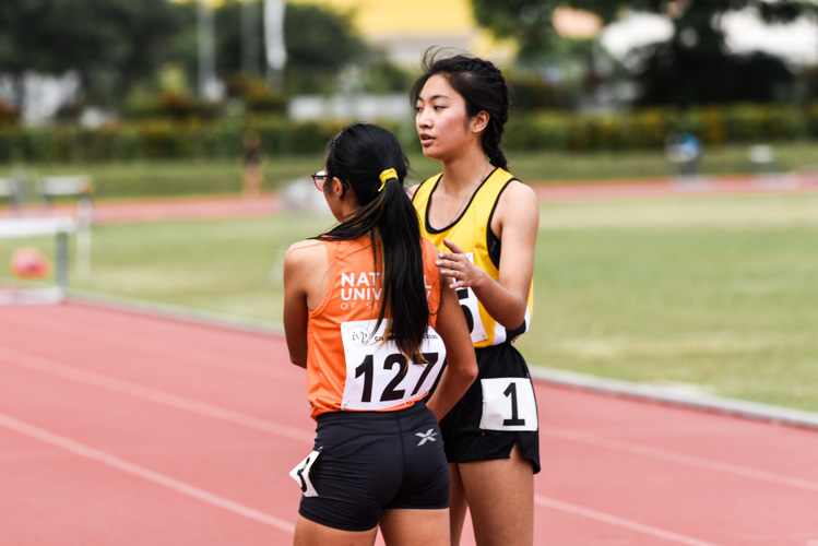 Singapore Polytechnic's Katherine Carino (#345), fourth-place finisher in the Women's 400m Hurdles, shares a moment with Celeste Goh of NUS after the race. (Photo 1 © Iman Hashim/Red Sports)