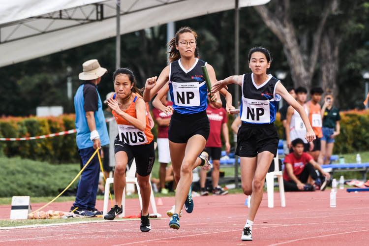 Ngee Ann Polytechnic's Joanna Seet hands over the baton to Candice Phaw between the second and third legs of the Women's 4x100m Relay final. (Photo 1 © Iman Hashim/Red Sports)