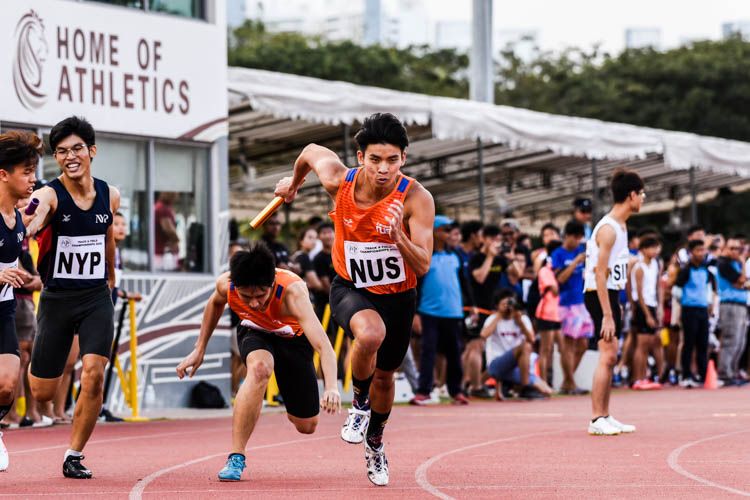 Justin Chan of NUS hands over to teammate Russell Kam between the first and second legs in the Men's 4x400m Relay first timed final. (Photo 1 © Iman Hashim/Red Sports)