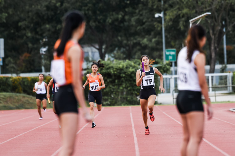 Grace Jo-ann Low of NUS and Clara Goh of TP running the first leg for their respective teams in the Women's 4x400m Relay timed finals. (Photo 1 © Iman Hashim/Red Sports)